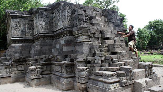 Arief (30) penjaga dan petugas kebersihan Candi Surowono saat membersihkan lumut dan kotoran di dinding relief Candi di Dusun Surowono, Desa Canggu, Kabupaten Kediri, Jawa Timur, Kamis (4/12). Pada musim hujan seperti saat ini perawatan candi ditingkatkan karena bebatuan relief  Candi mudah berlumut. Candi Surowono merupakan sebuah candi Hindu dari jaman Kerajaan Majapahit, diperkirakan dibangun pada tahun 1390 M sebagai tempat pendharmaan bagi Wijayarajasa, Bhre Wengker. ANTARA FOTO/Rudi Mulya/Rei/pd/14.