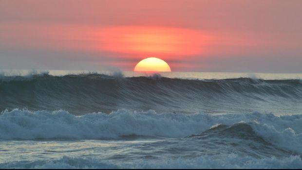 Ilustrasi matahari terbenam di laut