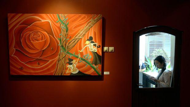 Seorang perempuan berada tak jauh dari lukisan yang dipamerkan di Galeri Seni 'House of Sampoerna' Surabaya, Rabu (28/1). Pameran lukisan bertajuk 'Legenda Cinta Nusantara' yang memajang 25 lukisan karya delapan pelukis yang tergabung dalam BRUSH 7+ tersebut, bermakna tentang legenda cinta rakyat yang sarat akan pesan moral dituangkan dalam imaji cinta kelokalan, dengan bentuk drawing, ilustrasi dan grafis. ANTARA FOTO/Eric Ireng/Rei/pd/15.