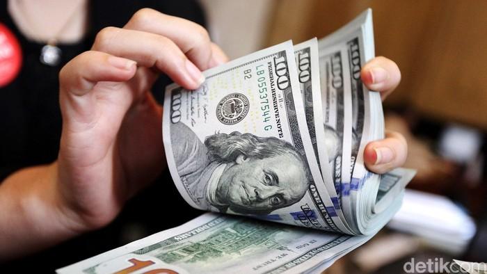 Merosotnya nilai tukar rupiah terhadap dolar AS yang menembus Rp 13.000,- menjadi alarm buat investor. Indeks Harga Saham Gabungan (IHSG) pun masuk dalam tren melemah yang cukup parah dalam beberapa hari terakhir. Seorang nasabah tengah menukar mata uang dolar di Bank CIMB Niaga, Jakarta, Selasa (16/06/2015). Rengga Sancaya/detikcom.