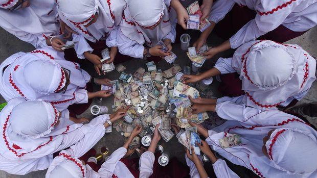 Sejumlah murid SD Al Falah Surabaya menghitung uang tabungan selama libur Lebaran ketika hari pertama masuk sekolah di halaman Sekolah mereka, Surabaya, Jawa Timur, Senin (27/7). Hasil uang tabungan para siswa tersebut selanjutnya diberikan kepada kaum duafa. ANTARA FOTO/Zabur Karuru/Rei/pd/15.