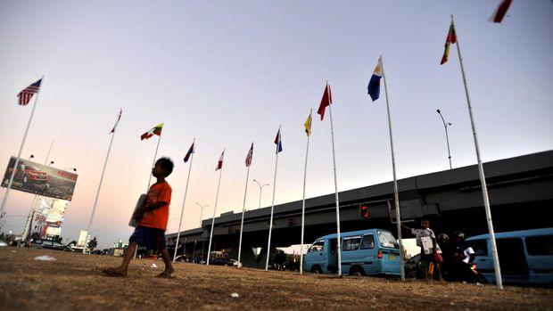 Bocah penjual koran melintas di dekat bendera negara-negara ASEAN di Makassar, Sulawesi Selatan, Selasa (1/9). Makassar akan menjadi tuan rumah pertemuan ASEAN Mayor Forum (AFM) atau Wali Kota se-Asia Tenggara yang berlangsung 8-10 September 2015. ANTARA FOTO/Yusran Uccang/foc/15.