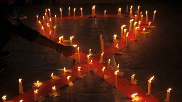 Mahasiswa Universitas Muhammadiyah (Unismuh) Makassar melakukan renungan dengan menyalakan lilin saat memperingati hari AIDS Sedunia di depan kampus Unismuh Makassar, Sulawesi Selatan, Selasa (1/12) malam. Aksi tersebut bertujuan memberikan pemahaman kepada masyarakat agar tidak melakukan diskriminasi terhadap penderita HIV AIDS. ANTARA FOTO/Abriawan Abhe/aww/15.