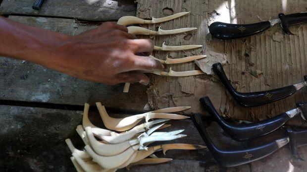 Perajin membuat hiasan senjata tajam tradisional Aceh (Rencong) di Desa Baet Lampout, Kecamatan Sibreh, Aceh Besar, Aceh, Selasa (19/1). Minimnya permintaan souvenir rencong di pasar wisata telah mengakibatkan jumlah pengrajin di kawasan sentra kerajinan rencong Aceh terus menurun dan mereka yang tersisa berharap ada kepedulian dari pemerintah daerah untuk mengatasi masalah tersebut. ANTARA FOTO/Irwannsyah Putra/aww/16.