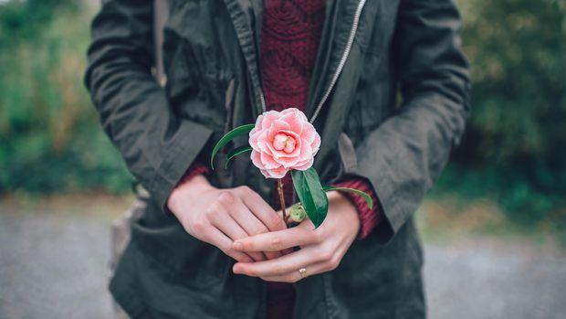 Ilustrasi perempuan memegang setangkai bunga