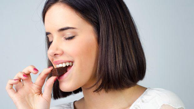 Portrait of beautiful girl eating chocolate cookies. Ilustrasi makan dengan mata terpejam prudkov/thinkstock