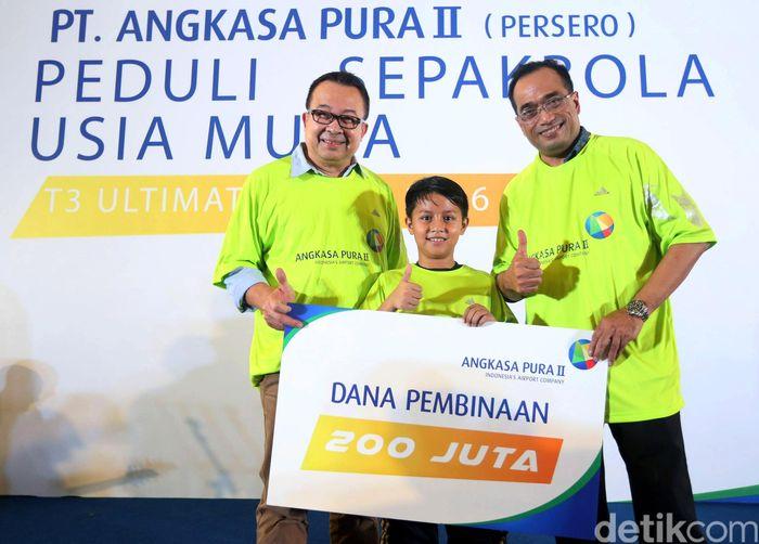 Pesepakbola cilik Tristan Alif (tengah) menerima beasiswa dari Komisaris Utama PT Angkasa Pura II Rhenald Khasali (kiri) dan Direktur Utama PT Angkasa Pura II Budi Karya Sumadi (kanan) di Terminal 3 Ultimate Bandara Soekarno Hatta, Tangerang, Jumat (3/6/2016).