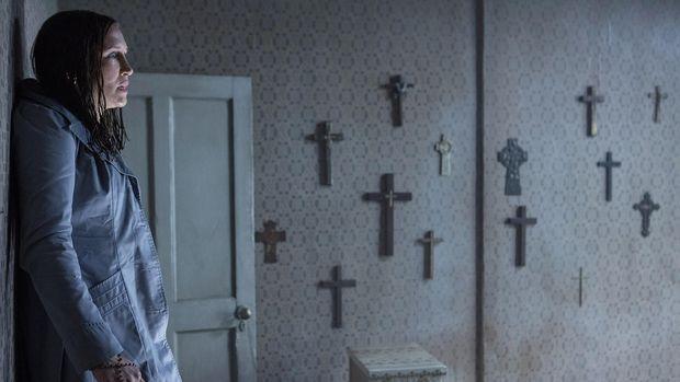 Lorraine Warren (Vera Farmiga) saat menghadapi setan yang memakai pakaian suster Gereja dalam kamar tidur Janet Hodgson (Madison Wolfe). Ia terpental ke tembok saat melawan setan itu.