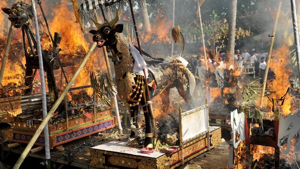 Sejumlah warga menyaksikan kremasi bagi anggota keluarganya dalam upacara Ngaben massal di Desa Batuan, Gianyar, Bali, Jumat (15/7). Ritual setiap 3 tahun tersebut melibatkan ribuan orang untuk memanjatkan doa dan menyaksikan kremasi terhadap 16 jasad warga setempat. ANTARA FOTO/Nyoman Budhiana/ama/16.