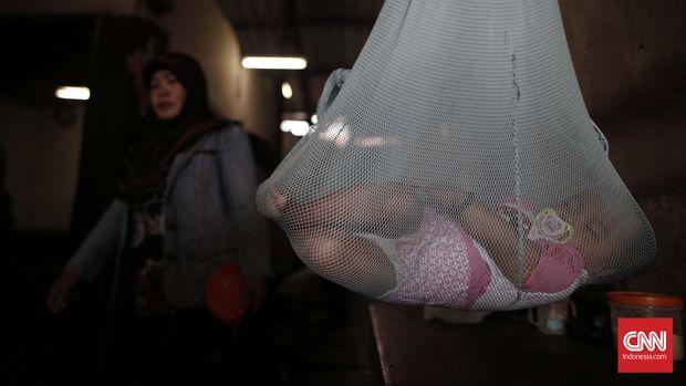 Seorang balita tidur di dalam ayunan di kawasan Pasar Sekanak Palembang, Sabtu, 16 Juli 2016. Yayasan Lembaga Konsumen Indonesia (YLKI) mengimbau pemerintah untuk segera memvaksinasi ulang balita yang positif mengonsumsi vaksin palsu. CNN Indonesia/Safir Makki
