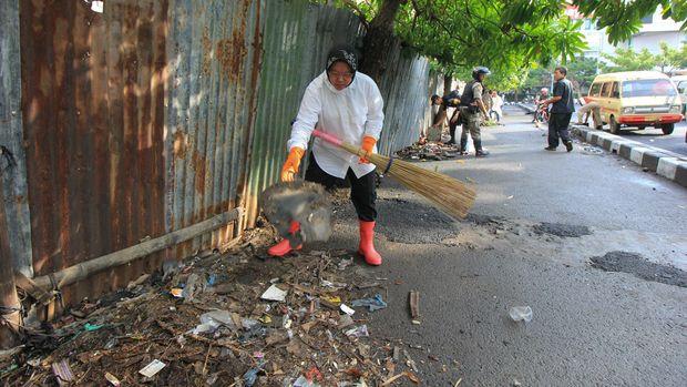 Wali Kota Surabaya Tri Rismaharini membersihkan jalan dari sampah di kawasan Jembatan Merah, Surabaya Jawa Timur, Senin (18/7). Kegiatan tersebut bertujuan agar kota Surabaya menjadi lebih bersih. ANTARA FOTO/Didik Suhartono/pd/16