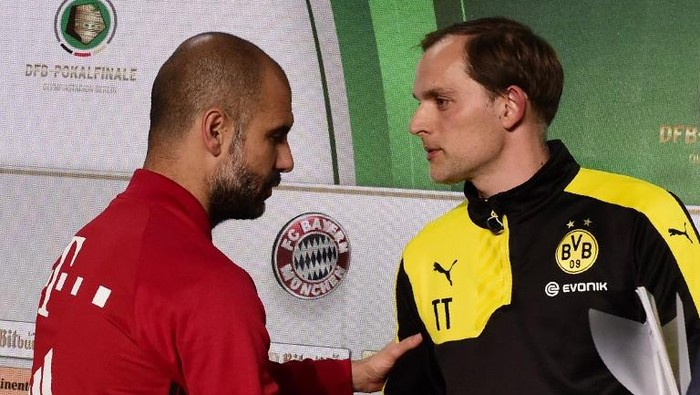 Dortmunds head coach Thomas Tuchel (R) greets Bayern Munichs Spanish head coach Pep Guardiola prior to a joint press conference on the eve of the German Cup (DFB Pokal) final football match Bayern Munich vs Borussia Dortmund at the Olympic stadium in Berlin on May 20, 2016. / AFP PHOTO / TOBIAS SCHWARZ