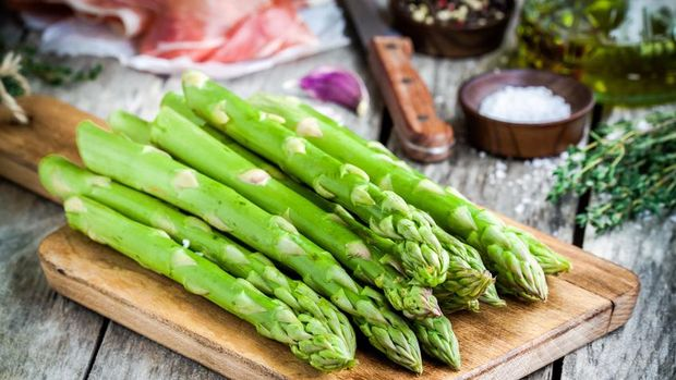Fresh organic asparagus on a cutting board with Parma ham on a rustic table