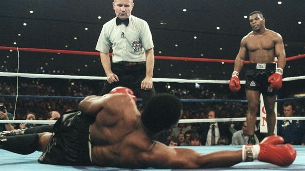 (TO GO WITH AFP STORY-BOXUS-TYSON-BERBICKChallenger Mike Tyson (R) looks down at his opponent, champion Trevor Berbick as referee Mills Lane (C) begins the count, after knocking him to the canvass in this 22 November, 1986 file photo during their WBC Heavyweight title bout in Las Vegas, NV. Tyson at the age of 20, KO'd Berbick in the second round to become the youngest ever heavyweight champion of the world.Twenty years after Mike Tyson battered Trevor Berbick to become the youngest heavyweight world champion in history, the