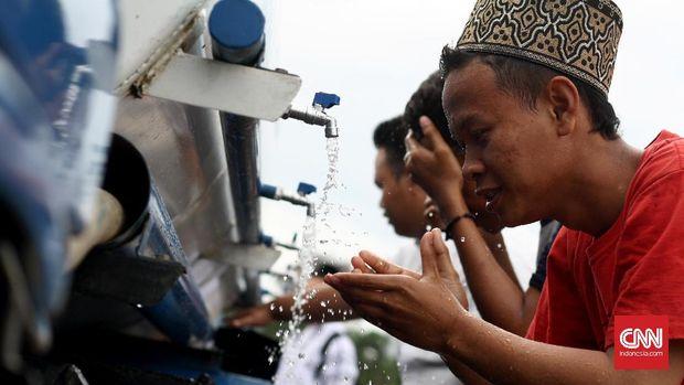 Para remaja FPI asal Cikampek wudhu di halaman Monas menggunakan truk air, Jakarta, Kamis 1 Desember 2016. Mereka tiba di Jakarta pada pukul 3 sore dengan jalan kaki. CNN Indonesia Ajeng Dinar Ulfiana