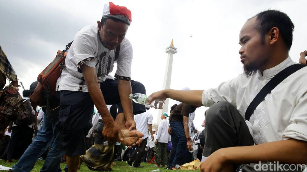 Massa Aksi 2 Desember Salat Jumat di Bawah Guyuran Hujan