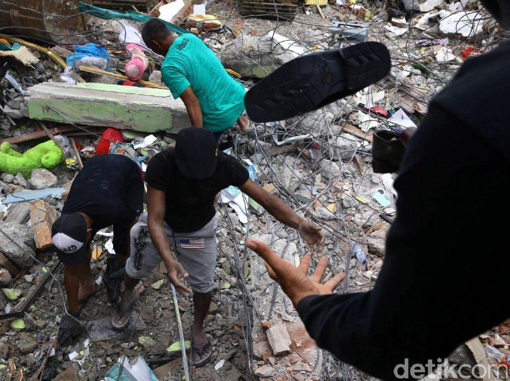 Warga Evakuasi Barang yang Tertimbun Reruntuhan