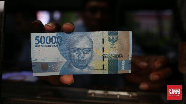 Petugas menujukkan gambar Djuanda Kartawidjaja dalam uang pecahan Rp50 ribu, di Blok M Square, Jakarta, 2016.