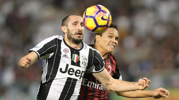 Juventus' Giorgio Chiellini (L) vies for the ball against AC Milan's Carlos Bacca during the Italian Super Cup final match between AC Milan and Juventus in Doha on December 23, 2016. / AFP PHOTO / KARIM JAAFAR