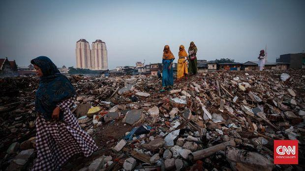 Warga melewati puing-puing menuju lokasi sholat idul fitri   yang diadakan warga gusuran kampung Akuarium, Penjaringan, Jakarta Utara, 6 Juli 2016. Aksi ini pun sebagai bentuk perlawanan mereka kepada pemerintah DKi Jakarta yang telah menggusur rumah mereka. CNN Indonesia/Safir Makki