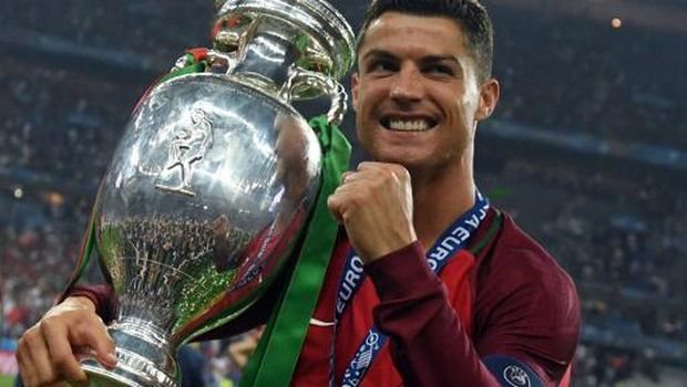 Portugal's forward Cristiano Ronaldo smiles while posing with the trophy after Portugal won the Euro 2016 final football match between Portugal and France at the Stade de France in Saint-Denis, north of Paris, on July 10, 2016. / AFP PHOTO / FRANCISCO LEONG