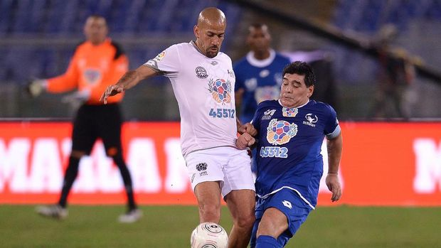 Argentinian football legend Diego Armando Maradona (R) vies with Argentina's  Juan Sebastian Veron during the 'Match of Peace - United for Peace' charity football match promoted by the Schools for Encounter foundation at the Olympic stadium in Rome on October 12, 2016.  / AFP PHOTO / FILIPPO MONTEFORTE