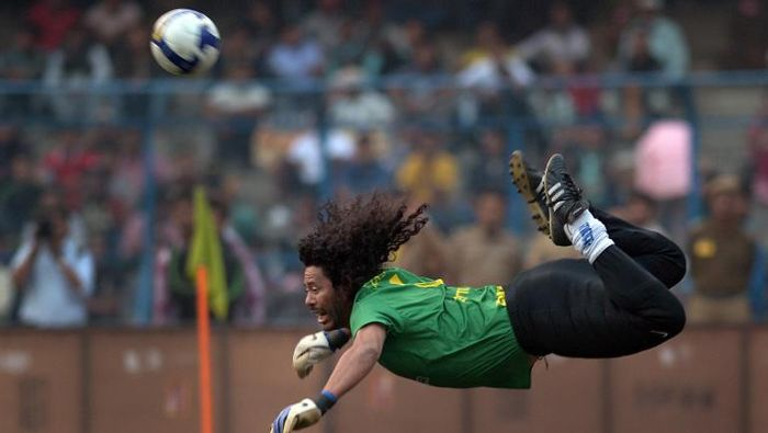 Former Colombian goolkeeper Rene Higuita kicks the ball to save a goal during an exhibition match between the Brazilian Masters and Indian All Stars in Kolkata on December 8, 2012. The Brazilian team won the match by 3-1. AFP PHOTO/ Dibyangshu SARKAR / AFP PHOTO / DIBYANGSHU SARKAR