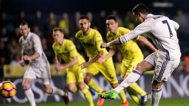 Real Madrid's Portuguese forward, Cristiano Ronaldo (R) shoots to score a goal during the Spanish League football match Villarreal CF vs Real Madrid at El Madrigal stadium in Vila-real on February 26, 2017.  / AFP PHOTO / BIEL ALINO