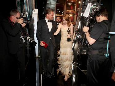 Leonardo DiCaprio tampak menggandeng Emma Stone di belakang panggung. Christopher Polk/Getty Images