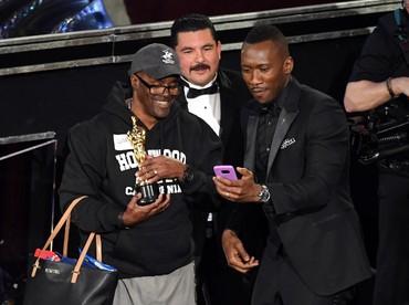 Tentunya pria tersebut merasa sangat beruntung bisa berfoto bersama aktor dan piala Oscar asli. Kevin Winter/Getty Images/detikFoto.