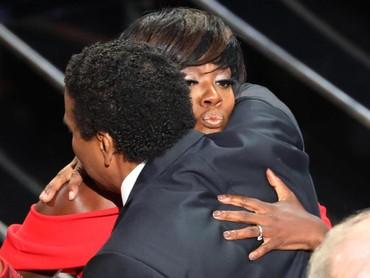 Pelukan hangat diberikan Denzel Washington pada Viola Davis karena berhasil memenangkan Best Supporting Actress. REUTERS/Lucy Nicholson