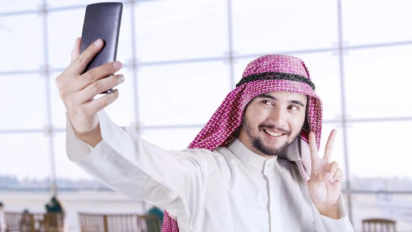 Portrait of Arabian tourist using a smartphone to take selfie picture in the airport