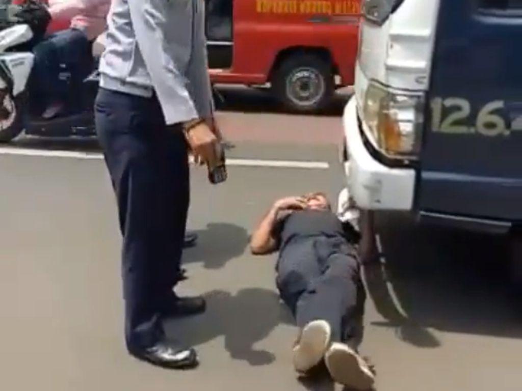 Tak Mau Mobilnya Diderek, Pria Ini Tiduran di Depan Mobil Petugas