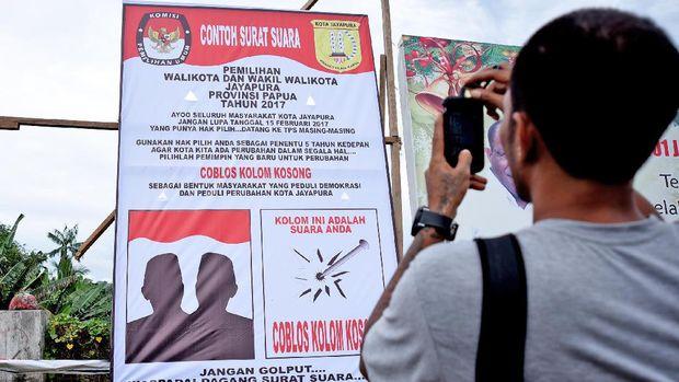 Warga mengabadikan baliho surat suara di depan Lapangan Trikora, Padang Bulan, Kota Jayapura, Papua, Rabu (8/2). Baliho ilustrasi surat suara satu calon tunggal ini mengajak masyarakat khususnya pemilih dalam Pilkada Kota Jayapura untuk mencoblos dengan cara yang tidak benar. ANTARA FOTO/Indrayadi TH/ama/17