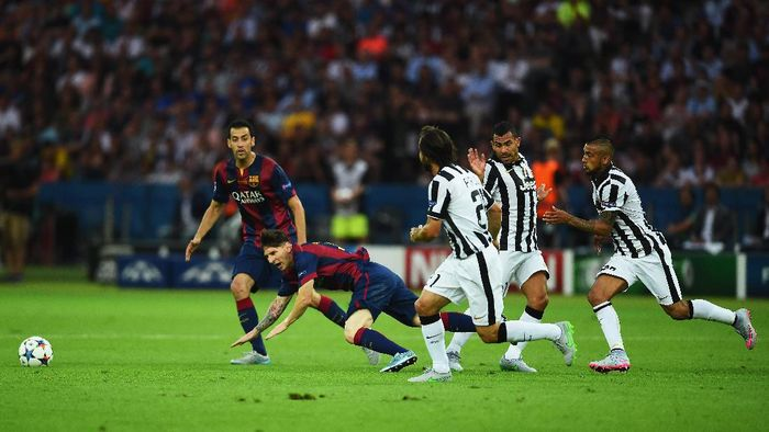 BERLIN, GERMANY - JUNE 06: Lionel Messi of Barcelona goes to ground after a challenge by Carlos Tevez of Juventus during the UEFA Champions League Final between Juventus and FC Barcelona at Olympiastadion on June 6, 2015 in Berlin, Germany.  (Photo by Laurence Griffiths/Getty Images)