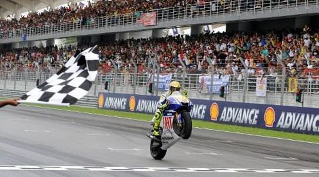 CORRECTING DETAILWorld Champion Italian rider Valentino Rossi of Fiat Yamaha celebrates defending his seventh Moto GP title the Malaysian Motocycle Grand Prix at the Sepang racing circuit on October 25, 2009. Defending world champion Rossi claimed the victory in wet track conditions, while Australian Casey Stoner won the Malaysian MotoGP race. The 30-year-old Rossi secured the title despite only coming in third. Spain's Dani Pedrosa was second. AFP PHOTO/SAEED KHAN / AFP PHOTO / SAEED KHAN