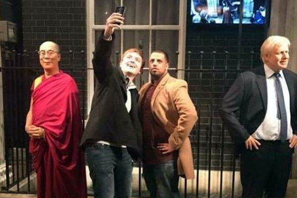 Traveler pretends to be a wax figure at Madame Tussauds Museum in London, England