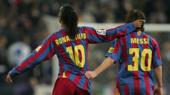 MADRID, SPAIN - NOVEMBER 19:  Ronaldinho (L) of  Barcelona celebrates with Lionel Messi after scoring a goal during the Primera Liga match between Real Madrid and F.C. Barcelona at the Bernabeu on November 19, 2005 in Madrid, Spain.  (Photo by Denis Doyle/Getty Images)