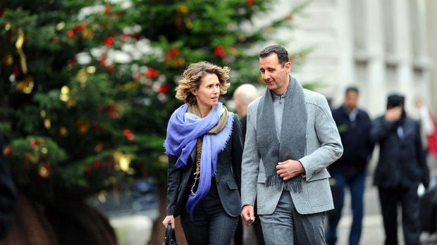 Syrian president Bashar al-Assad and his wife Asma walk in a street of Paris on December 10, 2010. Al-Assad is on a two-days official visit to France.  AFP PHOTO MIGUEL MEDINA / AFP PHOTO / MIGUEL MEDINA