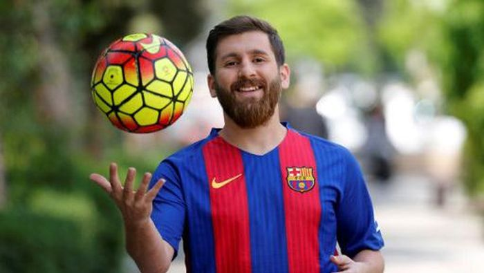 Reza Parastesh, a doppelganger of Barcelona and Argentinas footballer Lionel Messi, poses for a picture in a street in Tehran on May 8, 2017. / AFP PHOTO / ATTA KENARE