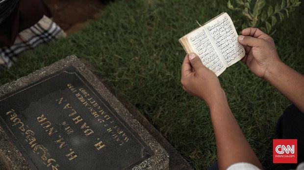 Peziarah sedang berdoa di kompleks pemakaman umum Karet Tengsin, Jakarta (21/5). Menjelang Ramadan, sebagian umat muslim berziarah ke makam untuk mendoakan dan membersihkan makam keluarga mereka yang sudah meninggal.  (CNN Indonesia/ Hesti Rika)