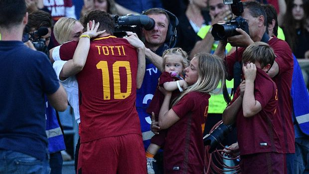 Roma's forward from Italy Francesco Totti (L) embraces his wife Ilary Blasi next to his children Cristian Totti (R), Isabel Totti and Chanel Totti during a ceremony to celebrate his last match with AS Roma after the Italian Serie A football match AS Roma vs Genoa on May 28, 2017 at the Olympic Stadium in Rome. Italian football icon Francesco Totti retired from Serie A after 25 seasons with Roma, in the process joining a select group of 'one-club' players. / AFP PHOTO / Vincenzo PINTO
