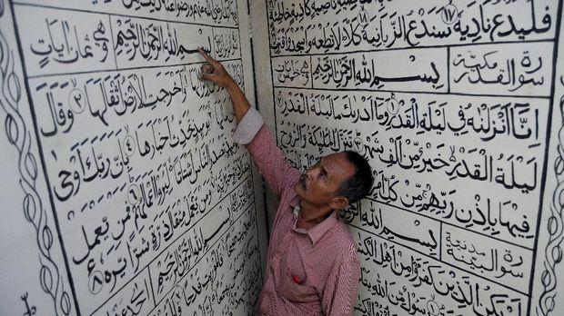 Warga mengamati tulisan Arab Alquran di Masjid Sapuro, Pekalongan, Jawa Tengah, Jumat (2/6). Alquran tulisan Arab berukuran panjang 2,4 meter dan lebar 2 meter yang terbuat dari triplek tersebut merupakan replika Alquran dari aslinya yang sebelumnya dihibahkan dari seorang komisaris polisi yaitu Moch Aswantary sekitar tahun 1970 di masjid tertua di Pekalongan tersebut. ANTARA FOTO/Harviyan Perdana Putra/ama/17