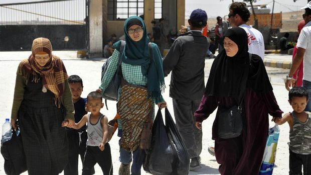 Leefa (4L) arrives at the Ain Issa camp, 50 kilometres north of Raqa, with other Indonesians after fleeing the Islamic State (IS) group's Syrian bastion on June 13, 2017.When Leefa set out from Indonesia for the Islamic State group's Syrian stronghold of Raqa, she says she thought she was headed to an earthly paradise for the faithful. She and her family imagined being surrounded by true believers and expected free healthcare and jobs paying salaries they could only dream of in Indonesia, the world's most populous Muslim-majority country. / AFP PHOTO / Ayham al-Mohammad