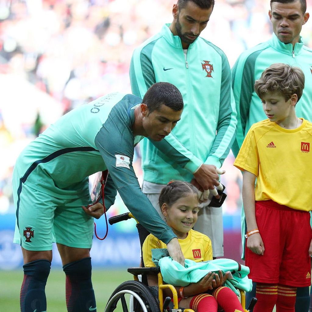 Kecupan dan Jaket Ronaldo untuk Bocah Pengiringnya yang Berkursi Roda