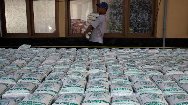 Warga membawa zakat fitrah berupa beras saat pembagian zakat di pendopo Sidoarjo, Jawa Timur, Jumat (23/6). Sekitar 3.000 paket zakat fitrah dari pegawai kabupaten Sidoarjo tersebut diberikan kepada masyarakat yang membutuhkan jelang hari raya Idulfitri. ANTARA FOTO/Umarul Faruq/foc/17.