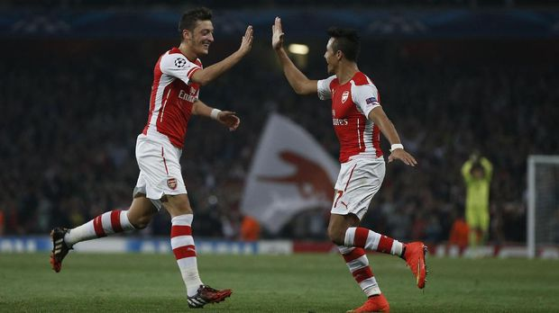 Arsenal's Chilean striker Alexis Sanchez (R) celebrates scoring his goal with Arsenal's German midfielder Mesut Ozil (L) during the UEFA Champions League, Group D football match between Arsenal and Galatasaray at The Emirates Stadium in north London on October 1, 2014. Arsenal won the game 4-1. AFP PHOTO / ADRIAN DENNIS / AFP PHOTO / ADRIAN DENNIS