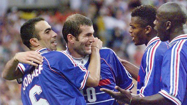 Photo prise le 12 juillet 1998 au Stade de France à Saint Denis, du milieu de terrain de l'équipe de France de football Zinedine Zidane (2eG), félicité par ses coéquipiers, Youri Djorkaeff (G), Marcel Desailly (2eD) et Lilian Thuram (D), après son deuxième but face à l'équipe du Brésil lors de la finale de la Coupe du Monde. French Zinedine Zidane (2nd L) is hugged by teammate Youri Djorkaeff (L) as they celebrate with Marcel Desailly (2nd R) and Lilian Thuram (R) after Zidane scored  a second goal for their team 12 July at the Stade de France in Saint-Denis, near Paris,  during the 1998 Soccer World Cup final match between Brazil and France. (ELECTRONIC IMAGE) / AFP PHOTO / GABRIEL BOUYS
