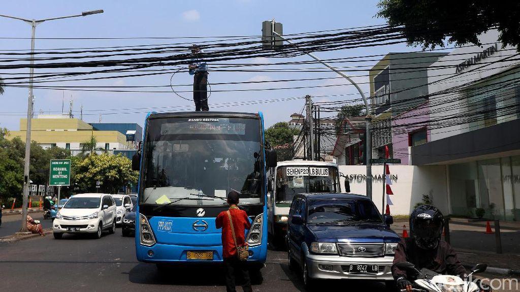 Aksi Petugas TransJ Atasi Kabel Melintang di Jalan