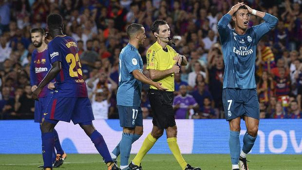 Real Madrid's Portuguese forward Cristiano Ronaldo (R) gestures after receiving a red card by referee Ricardo de Burgos Bengoetxea during the first leg of the Spanish Supercup football match between FC Barcelona and Real Madrid CF at the Camp Nou stadium in Barcelona on August 13, 2017.  / AFP PHOTO / Josep LAGO